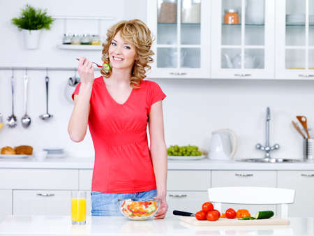 Beautiful young woman cooking healthy food and eating salad in the kitchen photo
