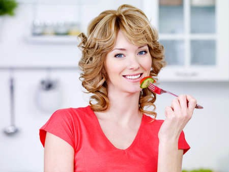 Portrait of beautiful smiling woman eating the salad in the kitchen photo