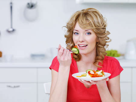 Young smiling woman eating salad in the kitchen - indoors photo