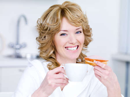 Laughing young beautiful woman with cup of coffee having breakfast - indoors photo