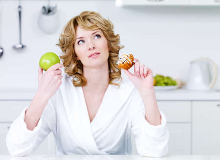 Thinking beautiful woman choosing between healthy food and caloric food - indoors photo