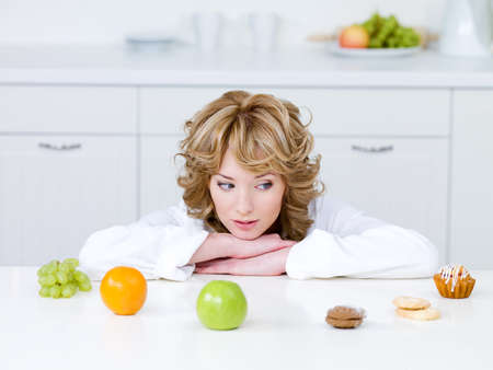 Beautiful young woman sitting in the kitchen and choosing between healthy fruits and tasty cakes