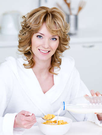 corn flakes: Portrait of beautiful happy smiling woman eating corn flakes in the kithcen Stock Photo