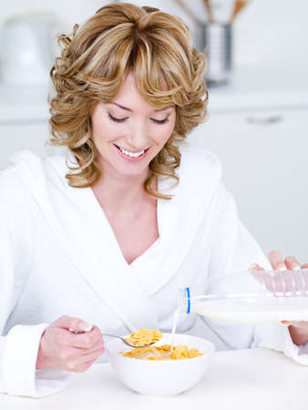 Smiling beautiful woman eating corn flakes in the morning - indoors photo