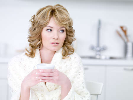 Portrait of woman sitting in the kitchen with cup of coffee - indoors photo