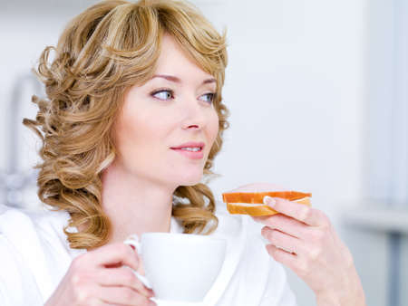 Pretty young woman with beautiful easy smile having breakfast in the kitchen photo