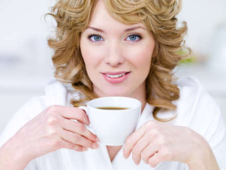Close-up portrait of pretty young beautiful blond woman with cup of coffee photo
