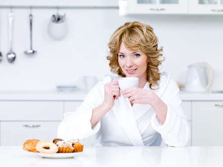 Beautiful young woman sitting in the kitchen and drinking coffee - indoors photo