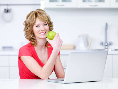 Woman with green apple and laptop sitting in the kitchen - indoors photo