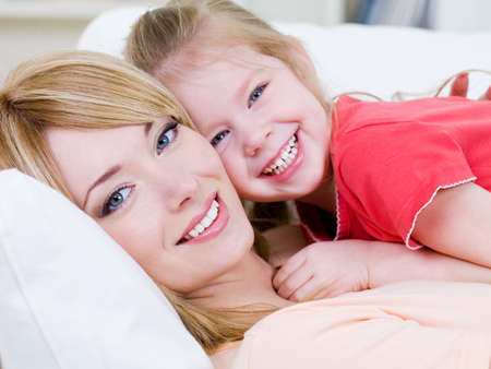 Close-up portrait of happy cheerful beautiful young mother with her little smiling daughter - indoors photo