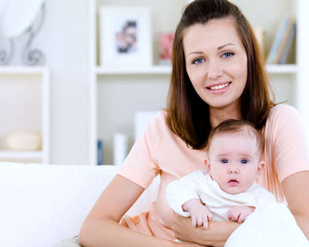 01: Portrait of happy young woman with newborn baby - indoors