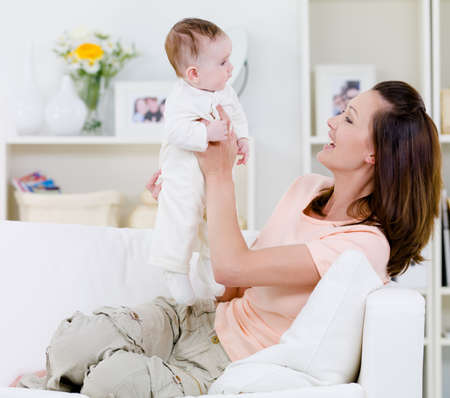 Happy young mother playing with her baby on the sofa - indoors photo