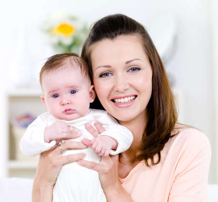 Close-up portrait of beautiful happy young woman with little baby - indoors photo