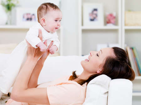 indoors: Beautiful young happy mother playing with her baby at home - indoors Stock Photo