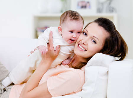 Young smiling happy mother with little baby on the sofa - indoors Stock Photo - 7294708