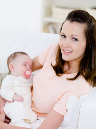 Portrait of young beautiful woman with sleeping baby on her hands - indoors photo
