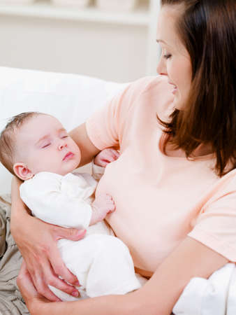 Beautiful little sleeping newborn baby on the womans hand - indoors photo