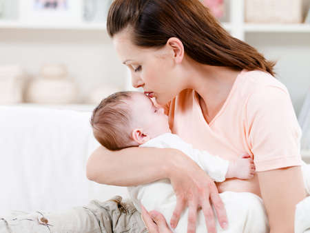 mum and baby: Young mother kissng her small sleeping newborn baby - indoors