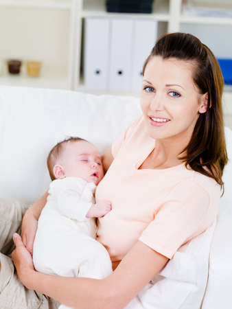Beautiful young woman holding slepping newborn baby - indoors photo