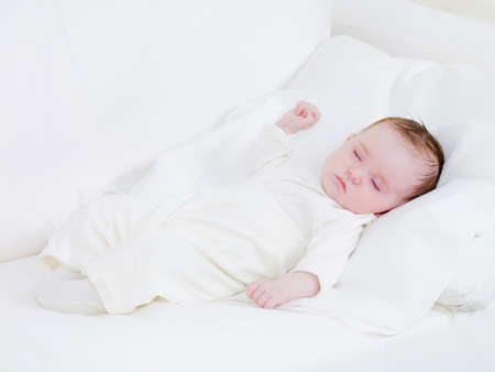 newborn baby: Innocence in sleeping newborn baby on the white sofa - indoors Stock Photo