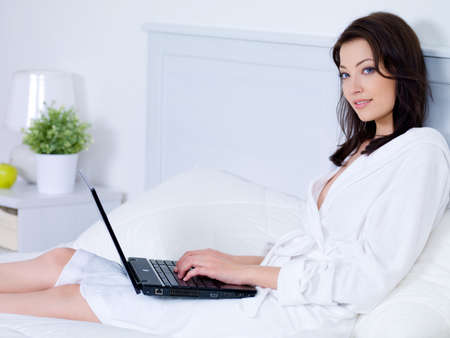 Beautiful young woman with attractive smile using laptop in bedroom - indoors photo