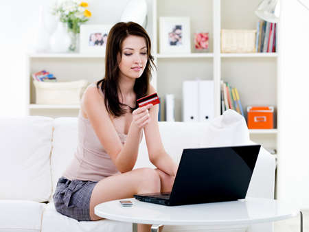 home shopping: Beautiful woman sitting at home and shopping with laptop and credit card  - indoors
