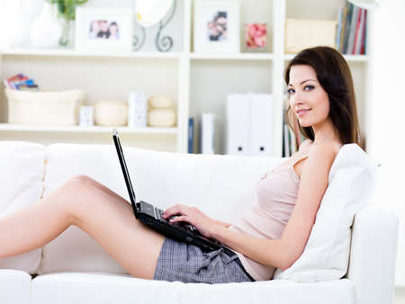indoors: Young woman with beautiful smile relaxing on the sofa anfd using laptop - indoors