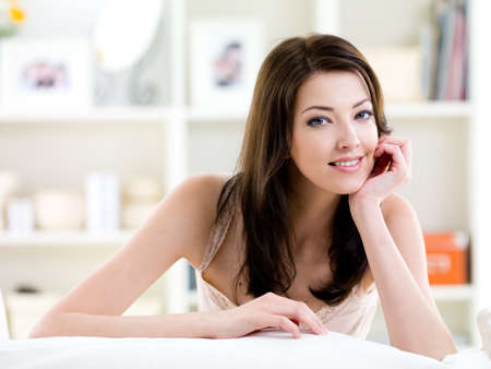 Beautiful young woman looking with easy attractive smile - indoors photo