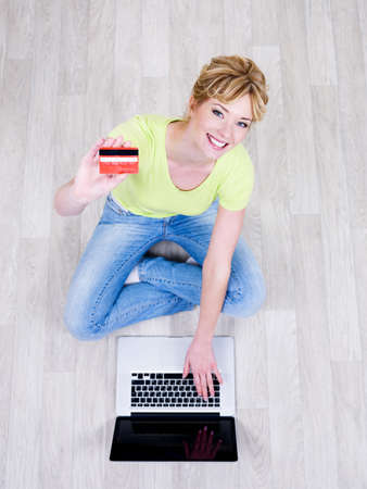Pretty beautiful young woman sitting on the floor with credit card and using laptop Stock Photo - 7299338