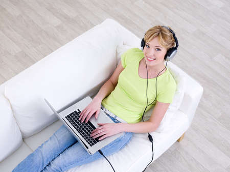 Smiling young beautiful woman listening music in headphone from laptop - high angle photo