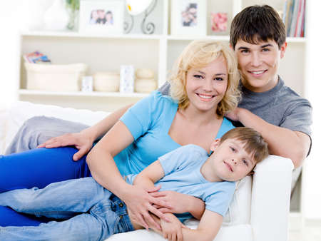 Portrait of happy cheerful family with little son with toothy smile - indoors photo