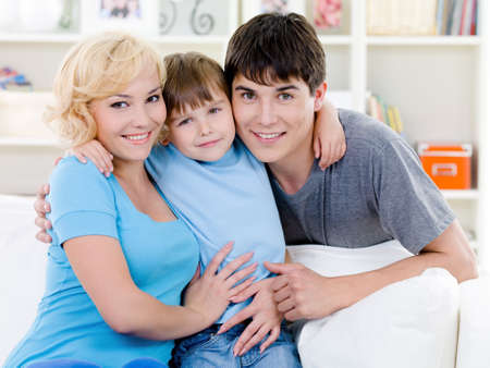 10s: Happy young smiling family with little son embracing - indoors