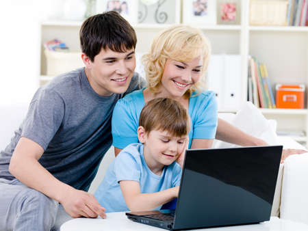 Happy smiling family with son using laptop at home - indoors photo