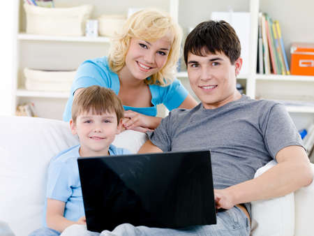 Portrait of young happy cheerful family with son and laptop - indoors photo