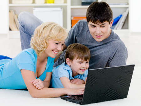 Beautiful happy young family with little son looking in laptop together - indoors photo