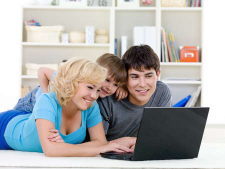 Modern laptop for young happy family with little son - indoors photo