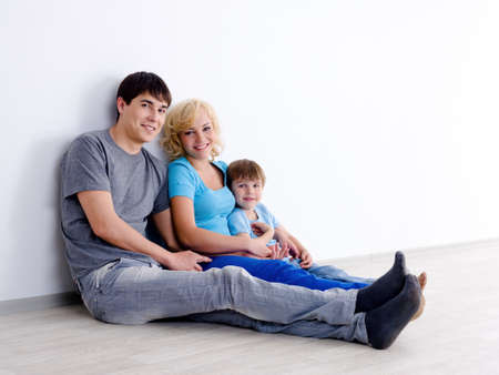 Happy family in casuals with little son sitting on the floor in empty room - indoors photo