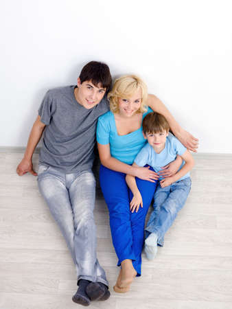 high angle: Young beautiful happy family with son sitting on the floor in the empty room - high angle
