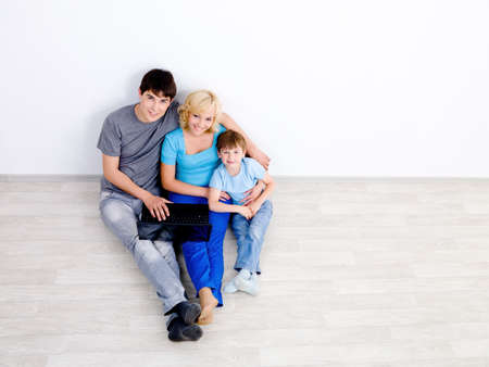 Happy young family sitting with laptop on the floor in emty room  together - high angle photo