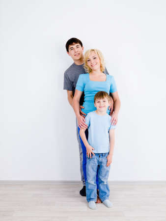 10s: Beautiful smiling family with son standing in line together in empty room Stock Photo