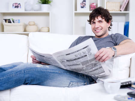 Portrait of handsome young man lying on the sofa with newspaper photo