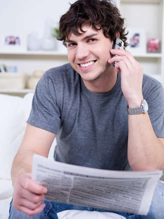 Portrait of happy handsome young man with mobile phone reading newspaper - indoors photo