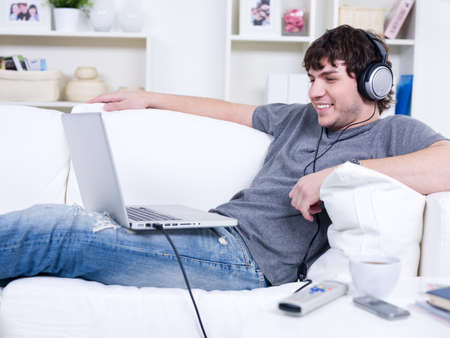 Man relaxing on the sofa and listening music on the laptop with headphone photo