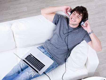Relaxation of young happy man lying on the sofa with laptop and listening music in headphone photo