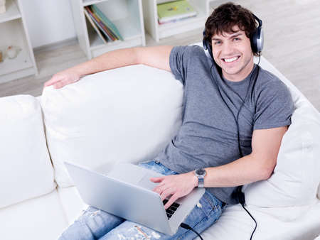 High angle portrait of smiling young handsome guy with laptop using headset photo