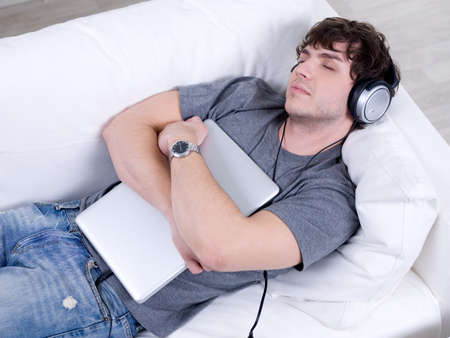 Man listening music in headphone and sleeping in embrace with laptop on the sofa photo