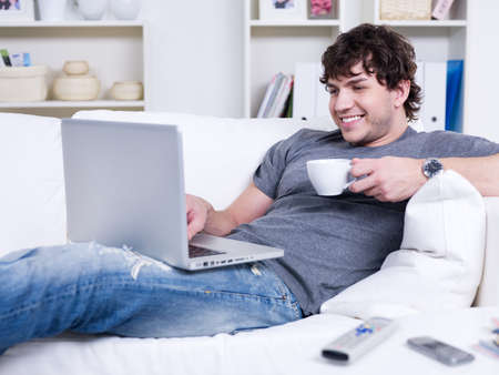 Handsome smiling young man with cup of coffee using laptop at home photo