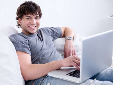 using computer: Portrait of young handsome smiling man working on the laptop at home