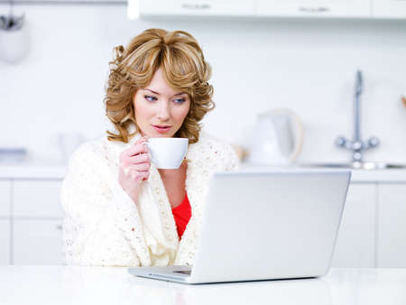 Young woman drinking coffee and using laptop in the kitchen - indoors photo