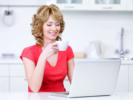 Portrait of beautiful woman in red sitting in the kitchen with cup of coffee and laptop photo